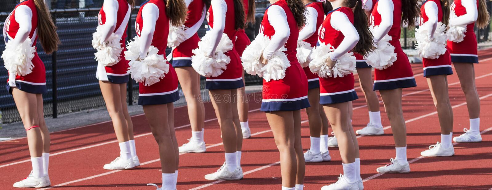 Cheerleaders cheering at a high school football game. Cheerleading squad performing a routine in fron of the home fans at a high school football game royalty free stock photo