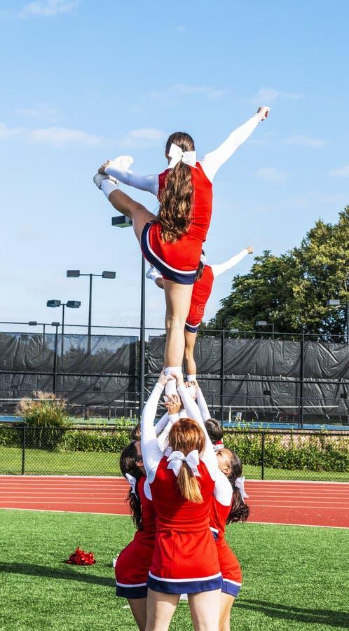 Cheerlearders γυμνασίου που κρατούν το συμπαίκτη επάνω στοκ εικόνα με δικαίωμα ελεύθερης χρήσης