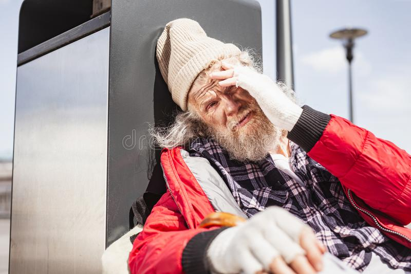Cheerless aged man sitting near the litter bin royalty free stock photo