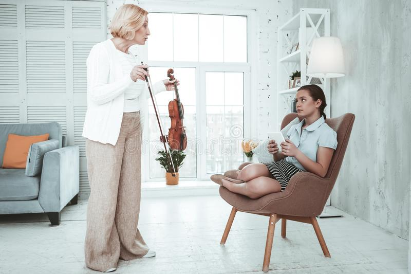 Cheerless blonde woman making her granddaughter play violin royalty free stock photography