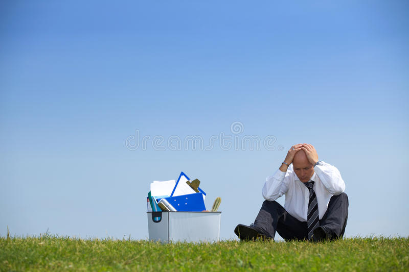 Cheerless businessman sitting next to basket full of files in park royalty free stock image