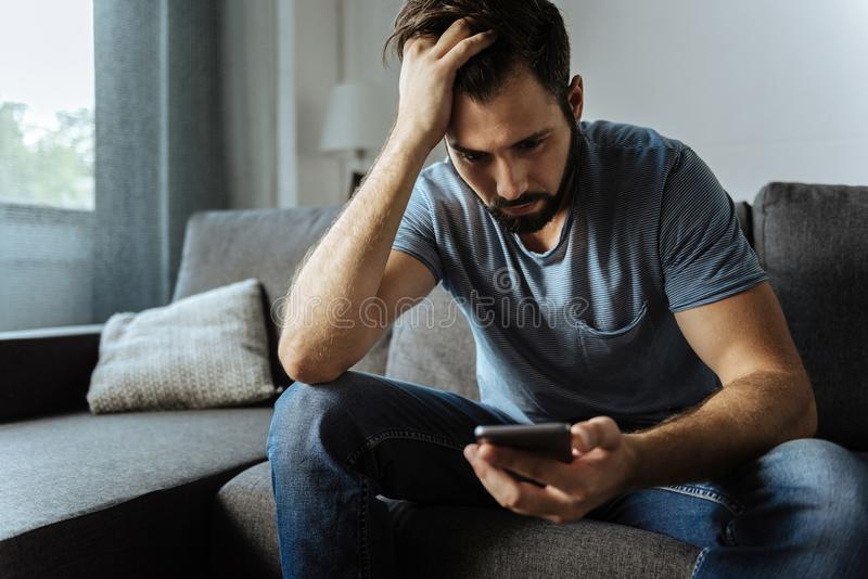 Cheerless handsome man looking at his smartphone screen royalty free stock photo