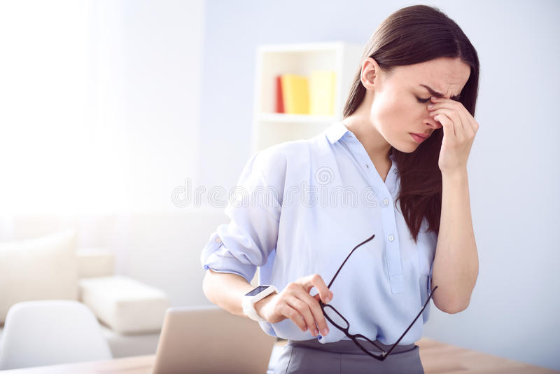 Cheerless tired woman standing in the office royalty free stock images
