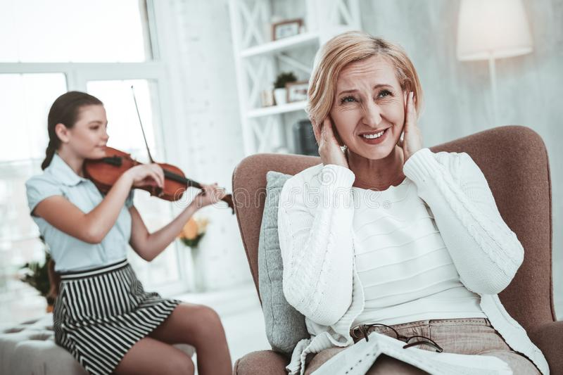 Cheerless unhappy blonde woman covering her ears royalty free stock photo