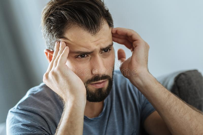 Cheerless unhappy man massaging his temples stock image