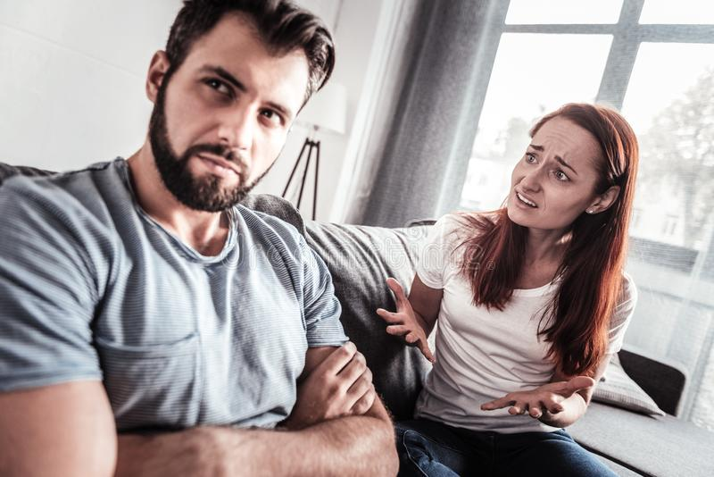 Cheerless unhappy woman talking to her husband stock images