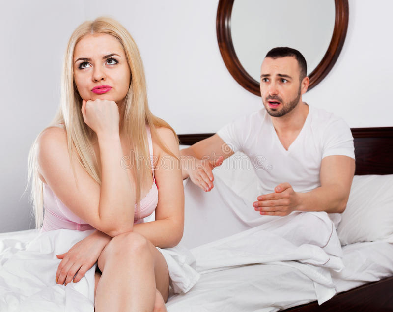 Cheerless woman turned away from man complaining. Cheerless beautiful women turned away from men complaining in bed stock image