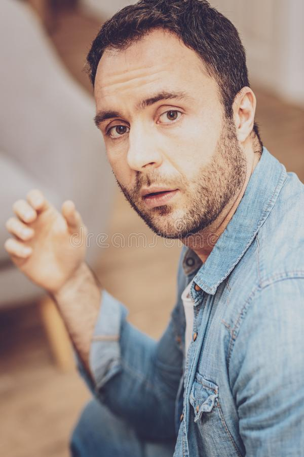 Cheerless young man looking at you stock photography