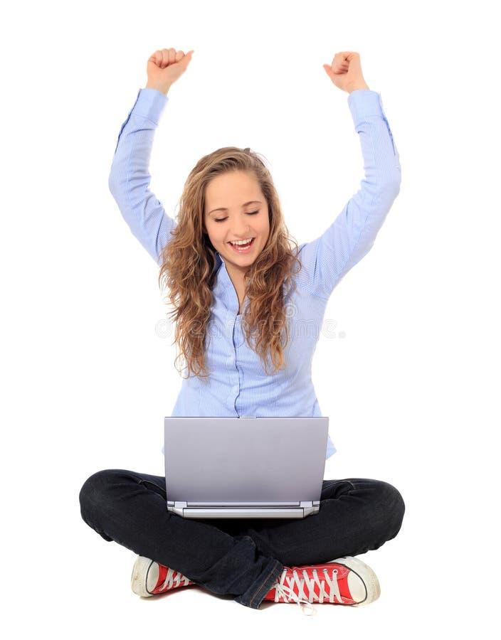 Cheers девочка-подростка пока использующ компьтер-книжку стоковое изображение
