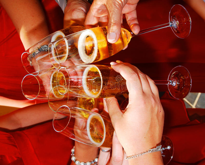 Cheers. Hands with champagne and glasses celebrate and cheers royalty free stock photography