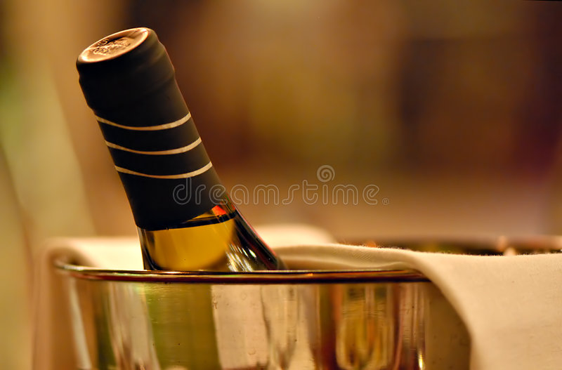 Cheers. ! Bottle of chardonnay in an ice bucket royalty free stock photos