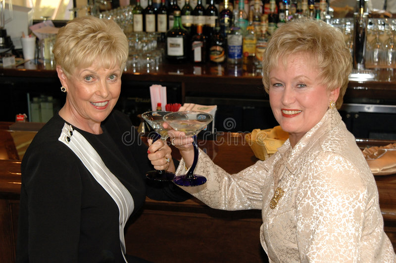Cheers in bar. Two well dressed senior women having drinks in a bar royalty free stock photo