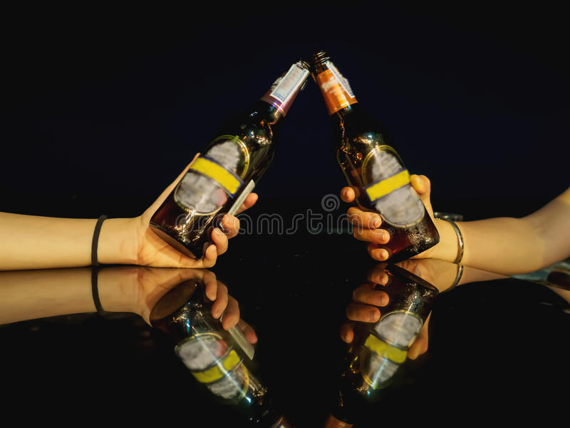 Cheers beer alcohol celebration making a toast at the beach during night time. stock photo