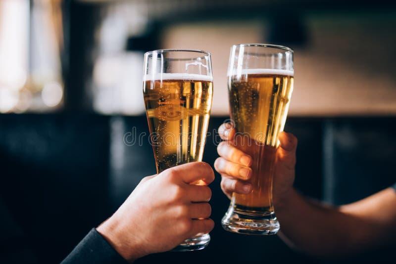 cheers Close-up van twee mensen in overhemden die met bier bij de barteller roosteren stock foto