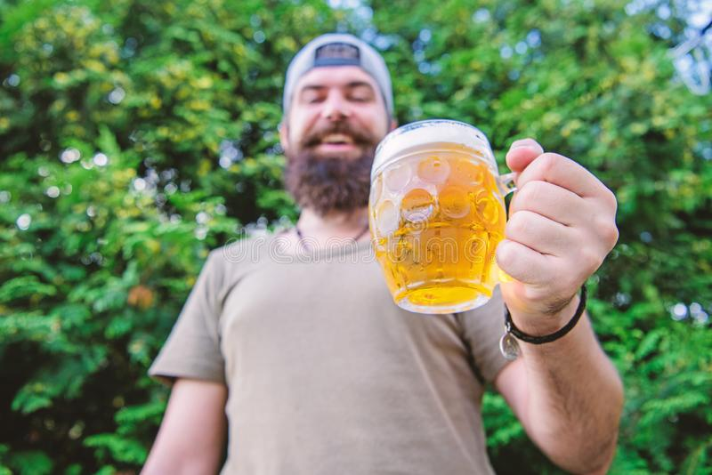 Cheers concept. Distinct beer culture. Hipster brutal bearded man hold mug cold fresh beer. Man relaxing enjoying beer. In summer. Alcohol drink and bar. Craft royalty free stock image