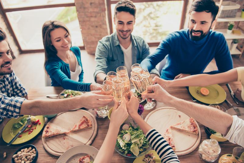 Cheers! High angle view of friends at birthday party clinking glasses with champagne and toasting, tasty dishes on the table stock image