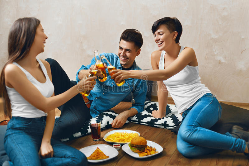 Cheers. People Toasting Beer, Eating Fast Food. Friends. Celebration, Leisure. Cheers. Group Of Happy Smiling Young People Toasting Beer Bottles And Eating Fast stock photo