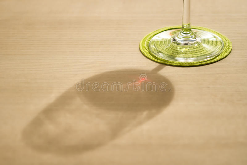Cheers with red wine. Shadow of a glass of red wine at wooden table royalty free stock images