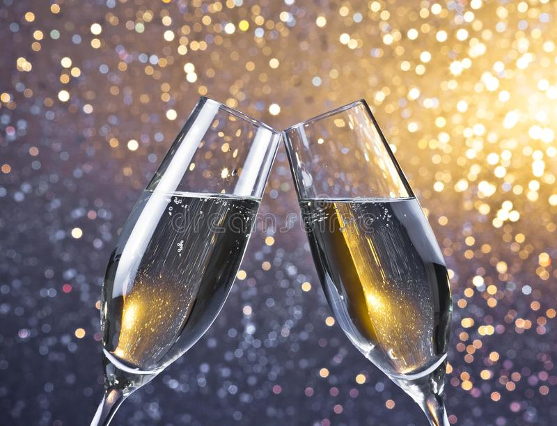 Cheers with two champagne flutes with golden bubbles on light bokeh background royalty free stock photography