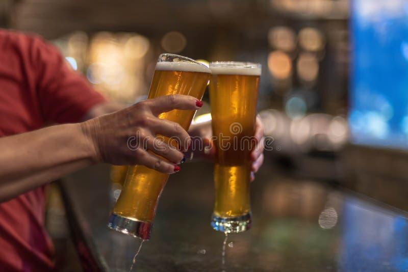 Cheersing med två kalla exponeringsglas av öl arkivbild