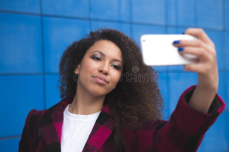 Cheert Selfie time Young happy lady in a spring vacation, walking in the city, drinking coffee, photographing herself on. A sun stock photos