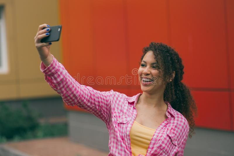 Cheert Selfie time Young happy lady in a spring vacation, walking in the city, drinking coffee, photographing herself on. A sun royalty free stock photos