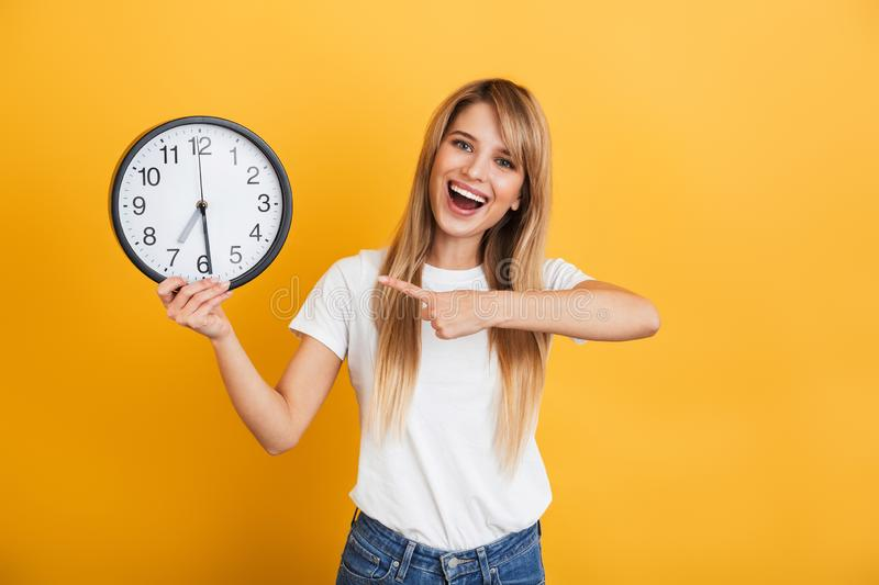Cheery young blonde woman posing isolated over yellow wall background dressed in white casual t-shirt holding clock pointing. Image of a cheery young blonde stock image