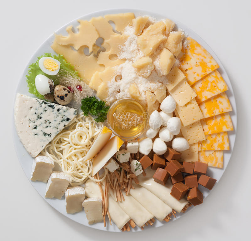 Cheese. Various types of cheese on a white plate with quail eggs and a cup of honey royalty free stock images