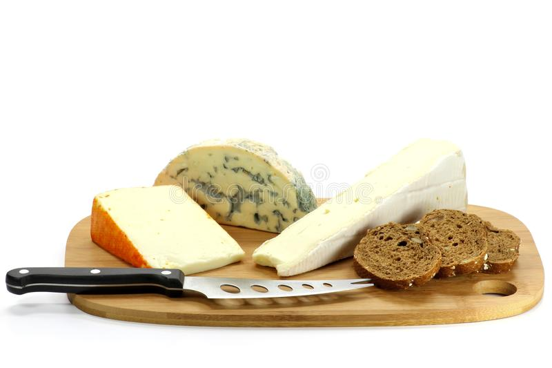 Cheese. Assortment of different soft cheeses on a wooden slat isolated on white background stock images