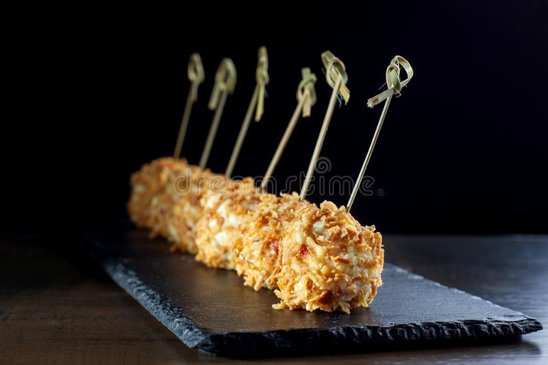 Cheese balls in breading, with natural bamboo skewers. Diagonal composition royalty free stock images