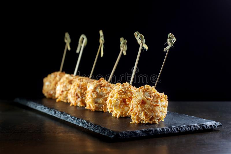 Cheese balls in breading, with natural bamboo skewers-2. Cheese balls in breading, with natural bamboo skewers. Diagonal composition stock photos
