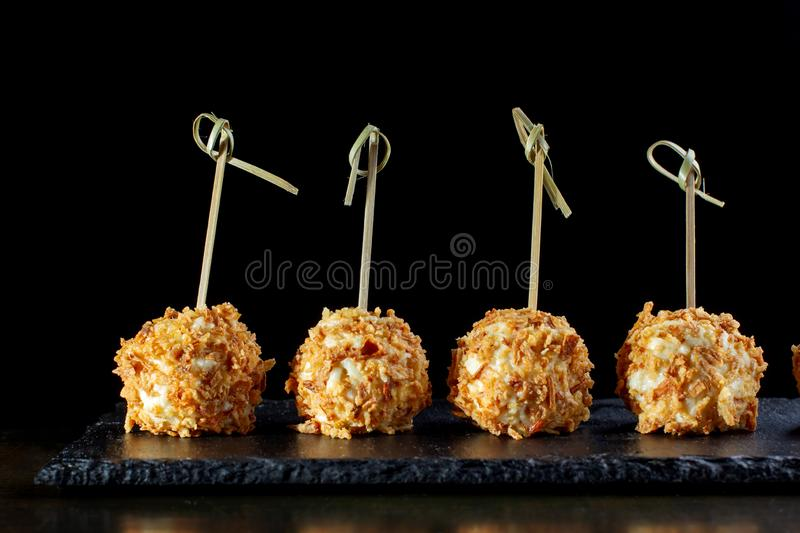 Cheese balls in breading, with natural bamboo skewers. Four balls, close-up stock image