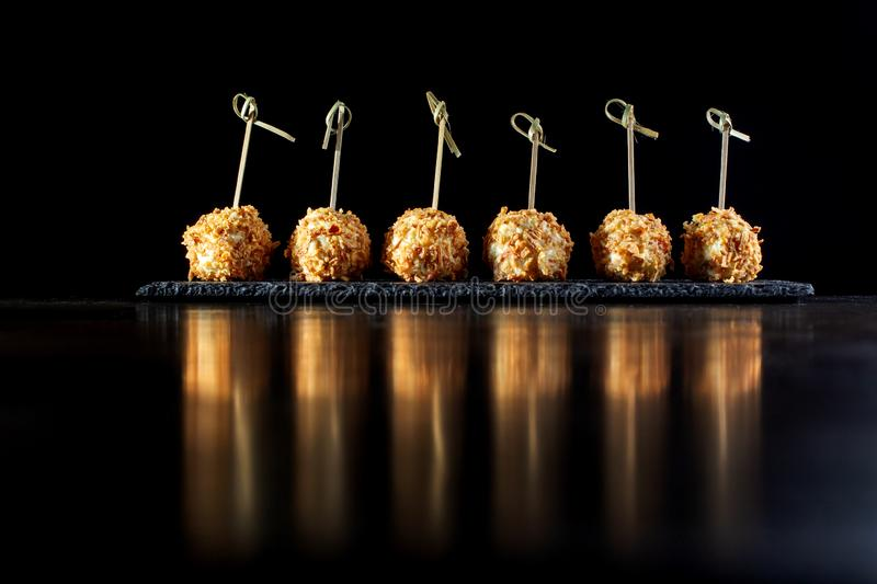 Cheese balls in breading, with natural bamboo skewers. Perfect reflection in the table cover stock photo
