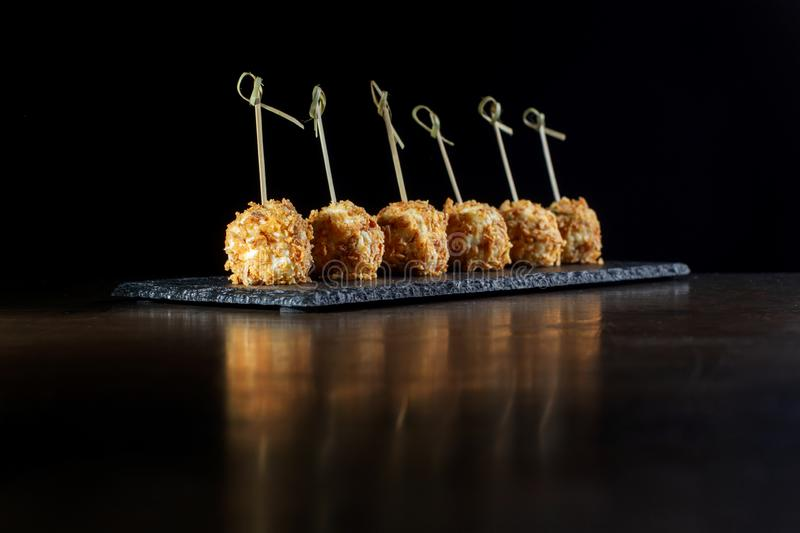 Cheese balls in breading, with natural bamboo skewers. Perfect reflection in the table cover. Diagonal composition stock image