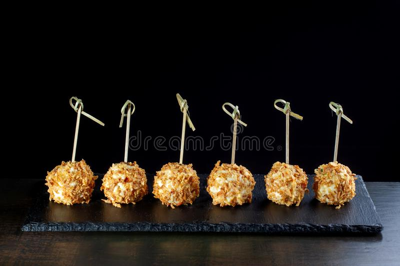 Cheese balls in breading, with natural bamboo skewers. Side view stock photography