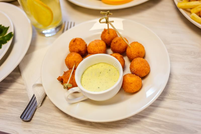 Cheese balls on a plate and sauce stock image