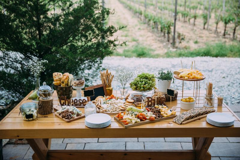 Cheese bar of several kinds of cheese, snacks, honey, nuts decorated on wooden table at the wedding party. Concept of stock image