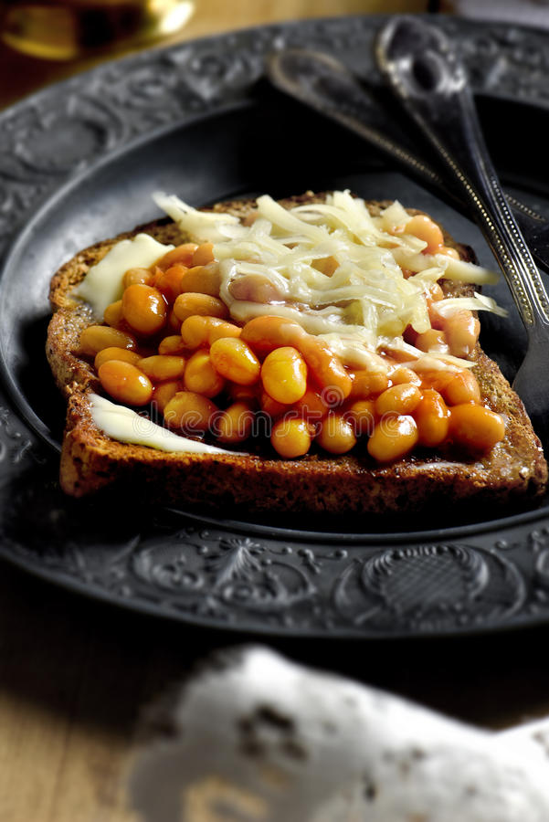 Cheese and Beans on Toast. Baked beans and grated cheese on buttered toast with selective focus and creative lighting. Copy space royalty free stock photo