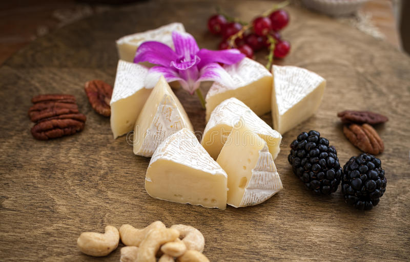 Cheese. Berries and nuts on a cutting Board royalty free stock images