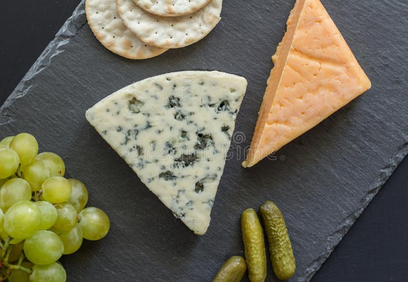 Cheese board with blue cheese, cheddar cheese, green grapes, crackers and pickled cucumbers on black slate - top view photograph stock photos