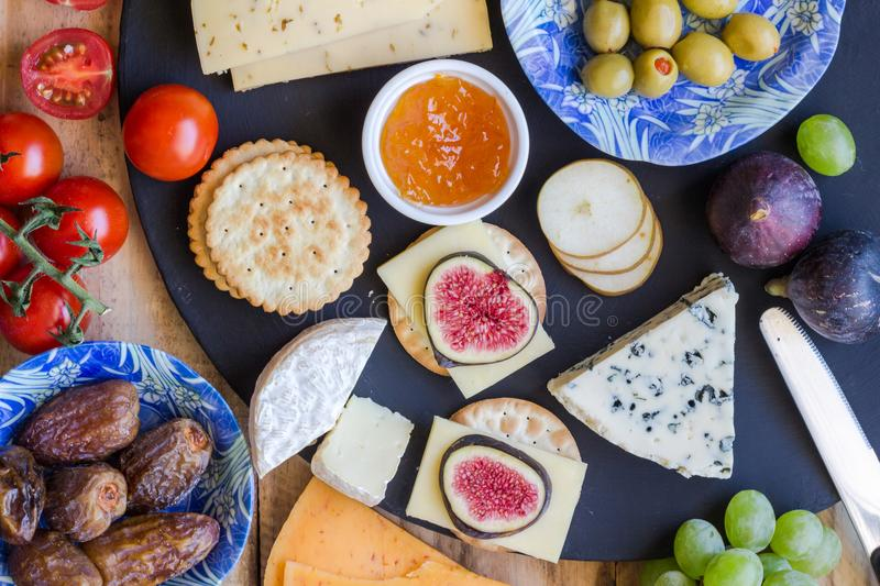 Cheese board close up with assortment of cheese, crackers, fruit royalty free stock photos