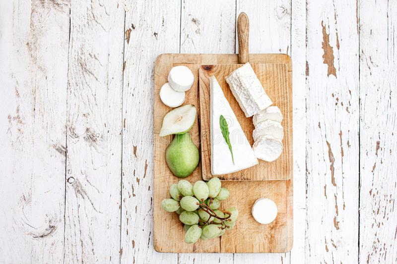 Cheese Board  with different cheese, pear and grapes on white  wooden background. Cheese platter Top view. Copy space royalty free stock photo