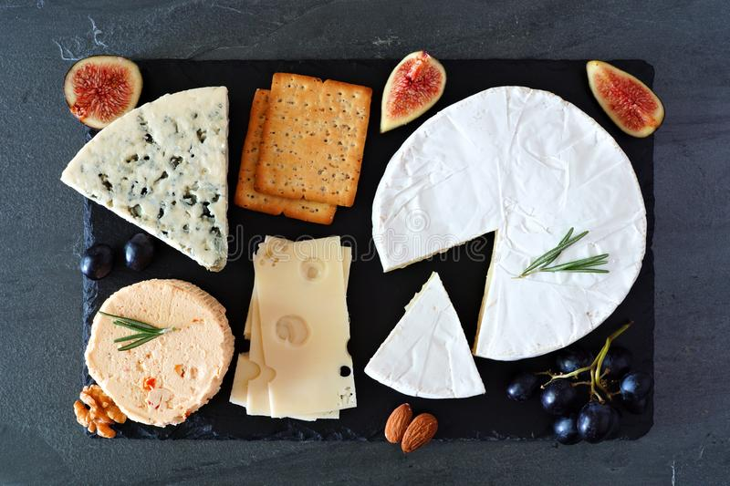 Cheese board with a selection of cheeses, crackers, figs and nuts, above view on a slate serving board royalty free stock images