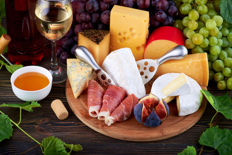 Cheese board and wine. On the table stock image