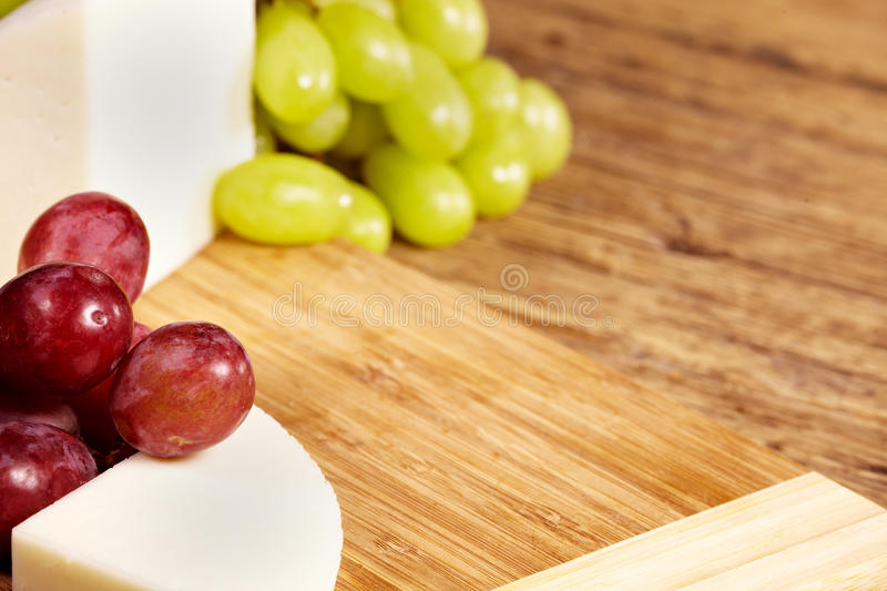 Cheese board on wooden table royalty free stock photography