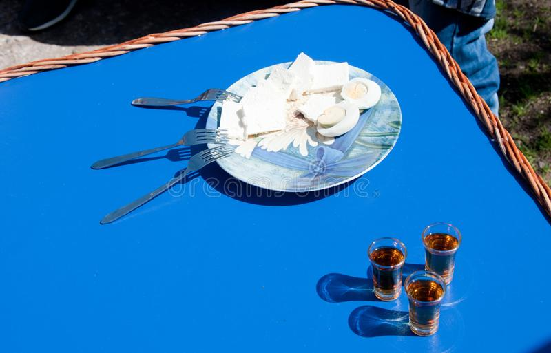 Cheese and boiled eggs on plate with three forks and three small glasses of brandy stock images