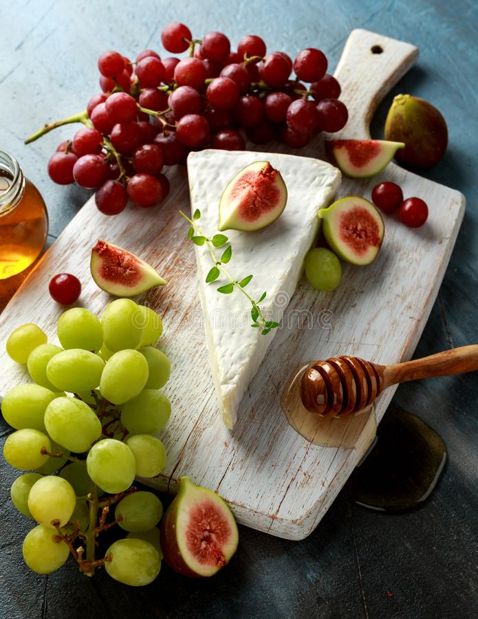 Cheese brie with figs, green and red grape and honey on white wooden board.  royalty free stock photography