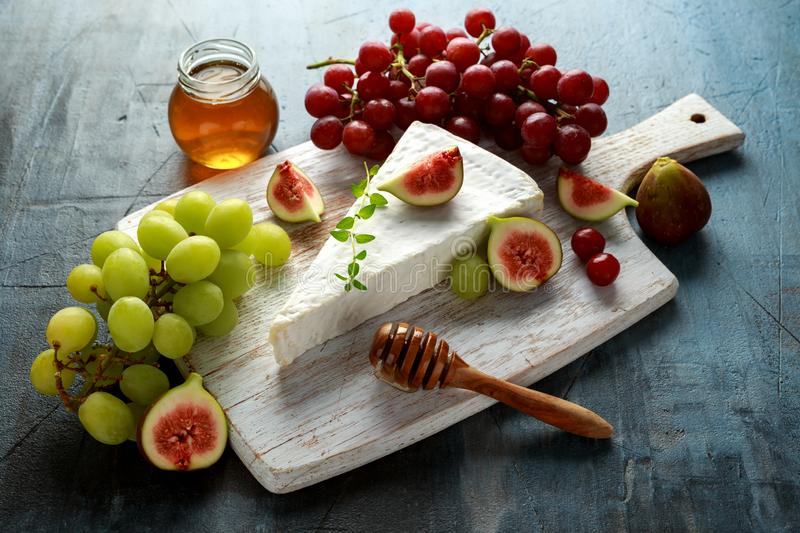 Cheese brie with figs, green and red grape and honey on white wooden board.  royalty free stock photos