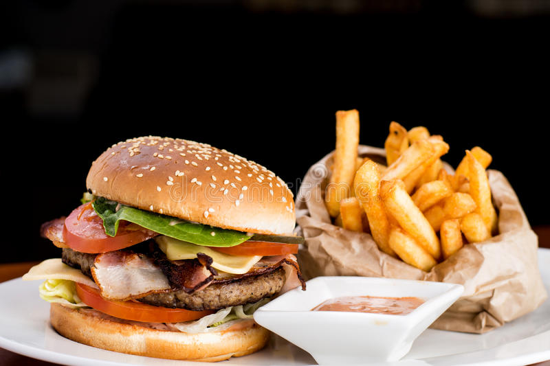 Cheese Burger and Fries. Juicy bacon burger with fries and souce un dark background stock photography