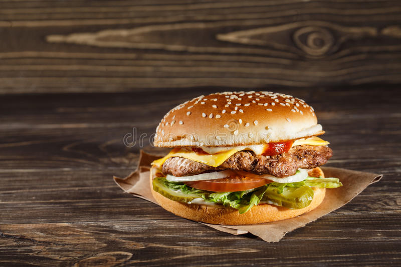 Cheese burger with grilled meat, cheese, tomato, on craft paper royalty free stock photo